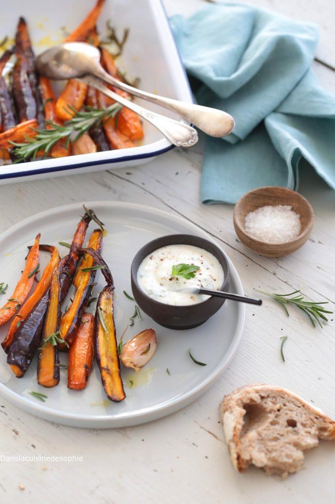 Assiette de carottes rôties servies avec une sauce au yaourt et aux herbes