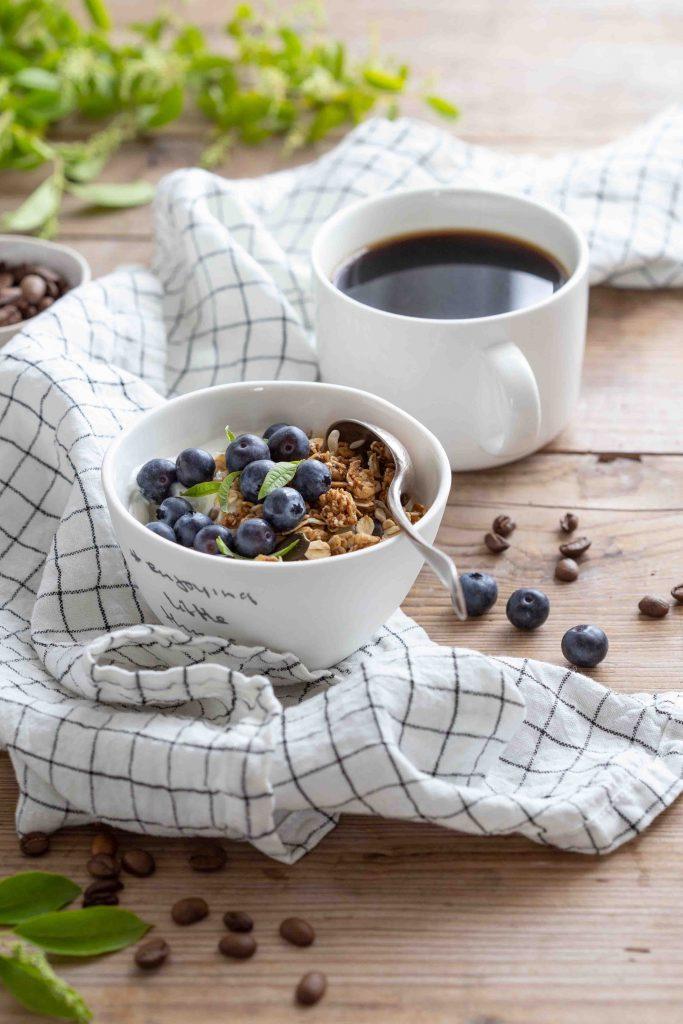 Bol de granola maison avec des myrtilles et tasse de café filtre