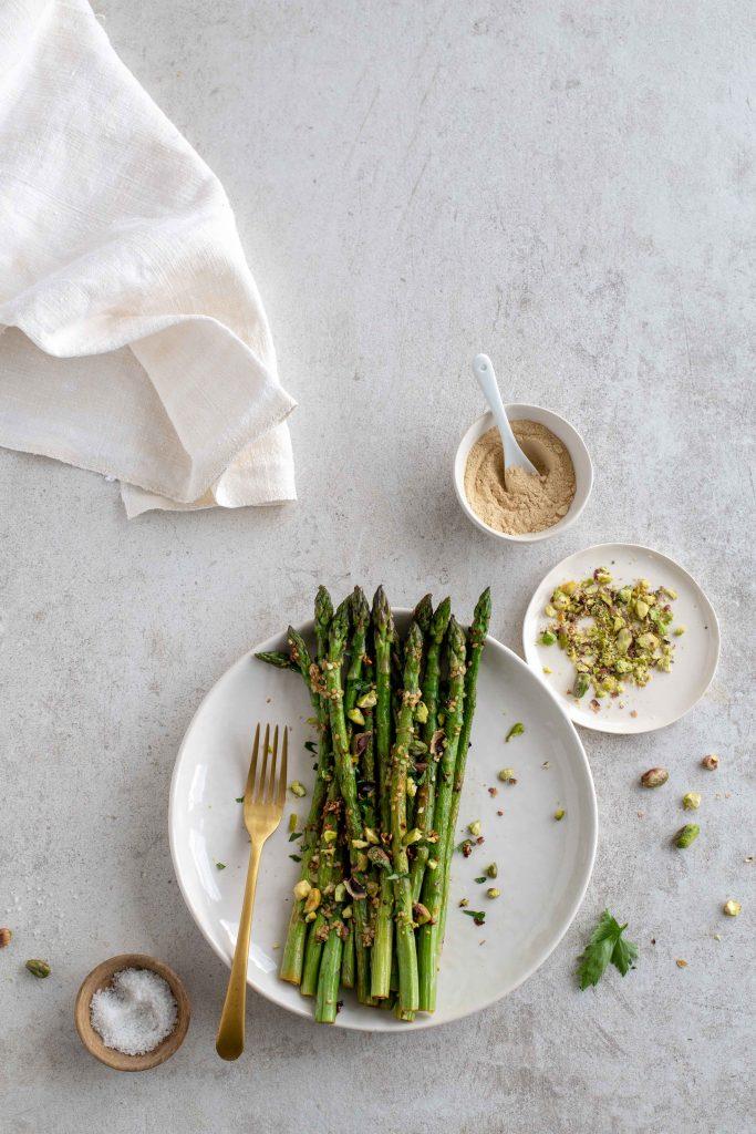 Assiette d'asperges vertes rôties, gingembre, pistaches et ail rôti