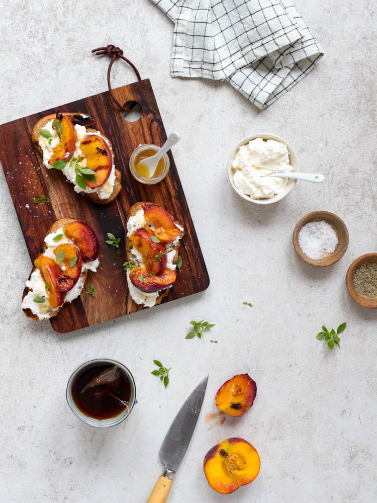 Planche de tartines de pêches rôties à l'huile d'olive et ricotta au miel