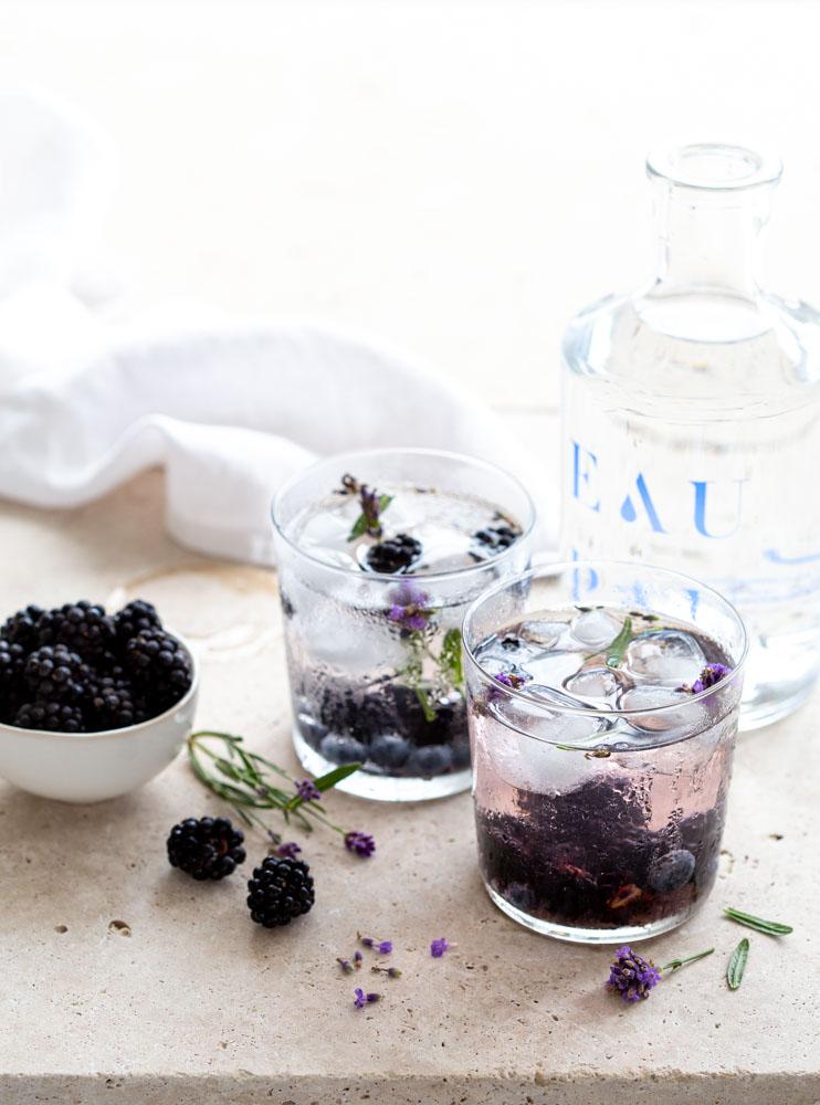 Verres d'eau détox mûres, myrtilles et lavande du jardin. Une boisson saine et rafraîchissante.