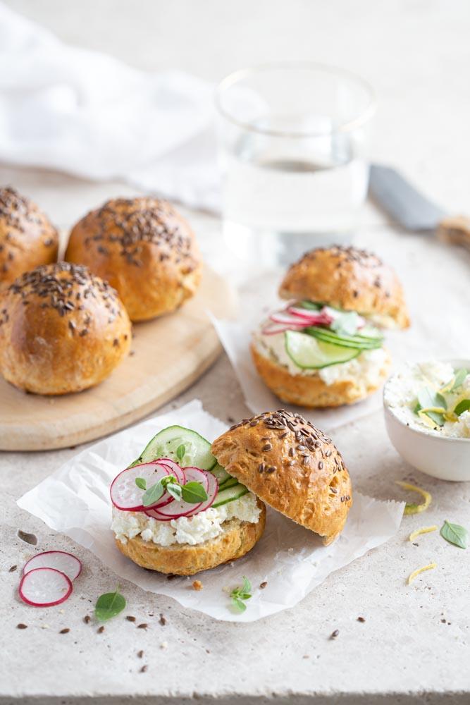 Petits pains au yaourt coupés en deux et garnis de fromage frais, radis et concombre en lamelles