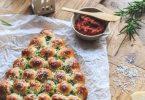 Sapin de noël en pâte à pizza garni de mozzarella et servie avec de la sauce tomate