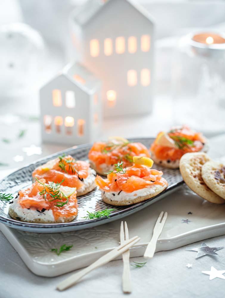 Plat présentant des blinis au saumon fumé, ricotta et au thé fumé : une association originale pour les fêtes de noël.