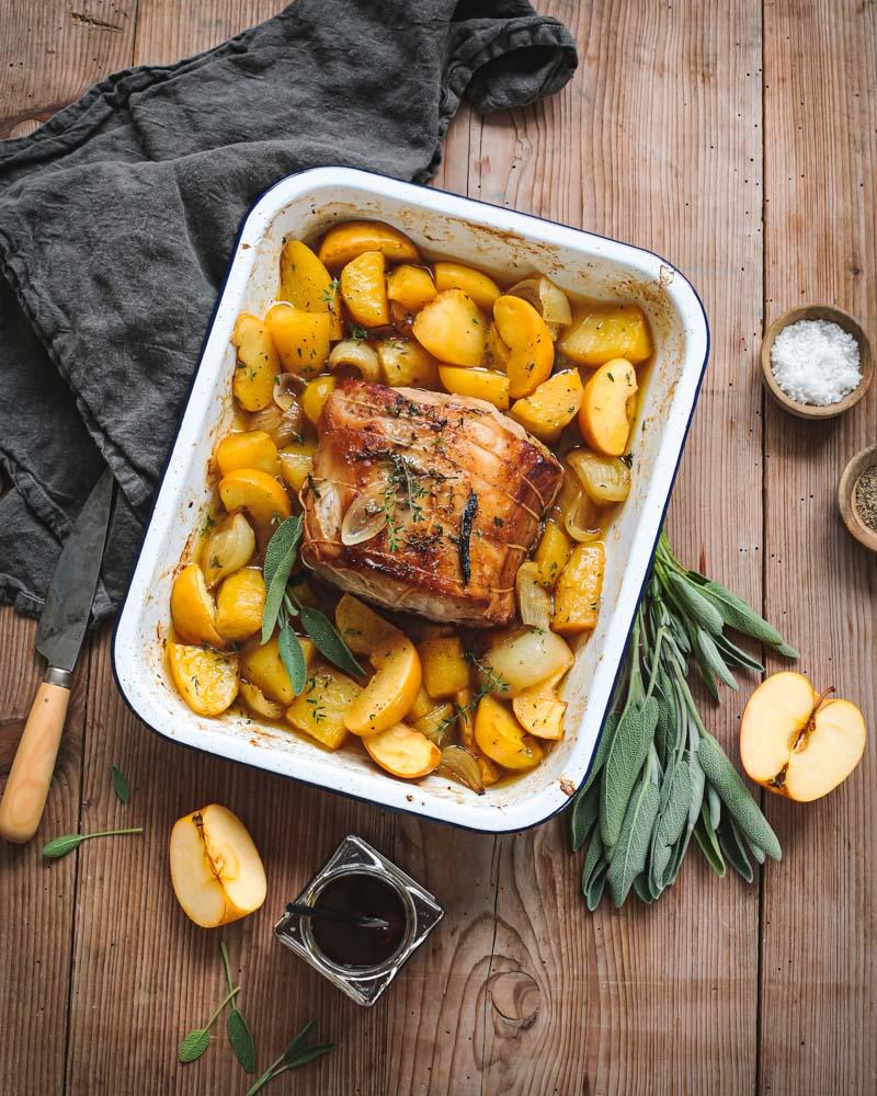 Plat de rôti de porc cuit au four à la boulangère avec des pommes de terre, des pommes, du miel et de la sauge.