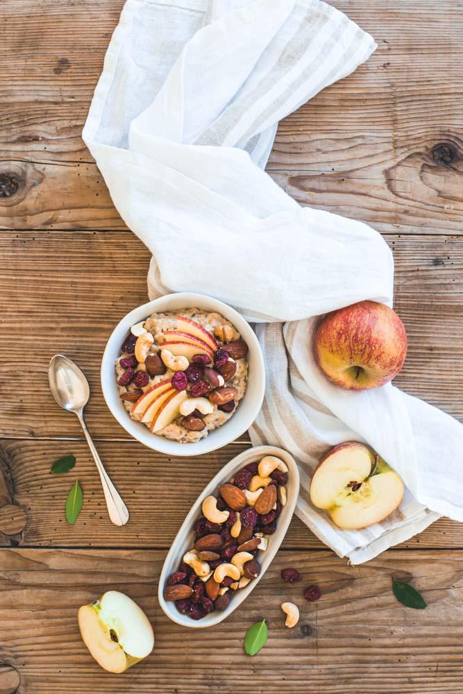 Bol de porridge aux dattes, gingembre, quartiers de pommes agrémenté de fruits secs et cranberries