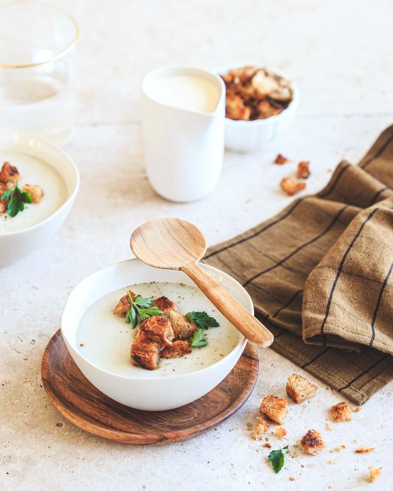 Bol de velouté de topinambours agrémenté de croûtons de pain au levain et de persil plat. En finition, un peu de crème pour le côté gourmand.