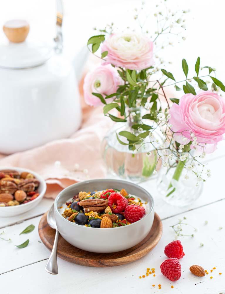 Bol composé de yaourt végétal, fruits rouges frais, mélange de noix et de pollen pour le petit déjeuner