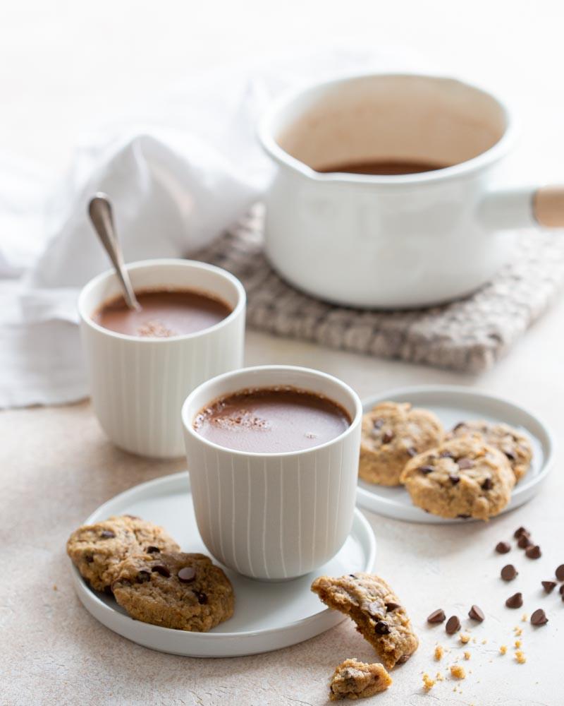 Tasses de chocolat chaud à l'ancienne accompagnées de cookies vegan aux pépites de chocolat et beurre de cacahuète pour un goûter gourmand.