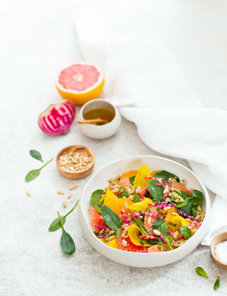 Assiette de salade vegan simple et rapide à faire composée de quinoa et couscous en perles, feuilles d'épinards, pamplemousse, oranges et betteraves chiogga.