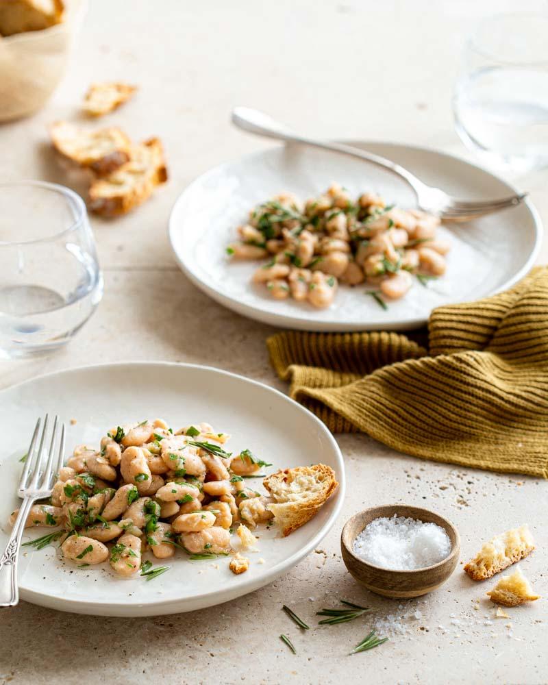 Assiettes de haricots tarbais en salade avec une vinaigrette au persil et romarin. Une recette confinement à servir avec du pain grillé.