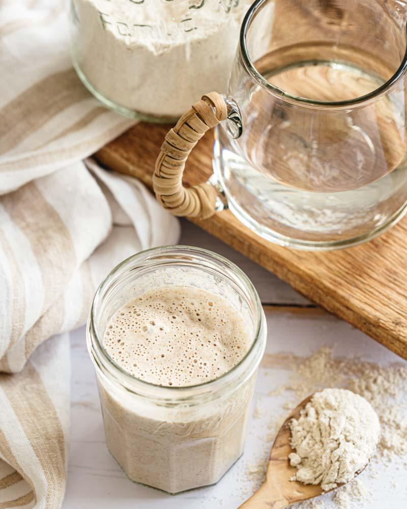 Bocal de levain naturel rafraîchi en train de faire des bulles et prêt à être utilisé pour confectionner du pain maison.