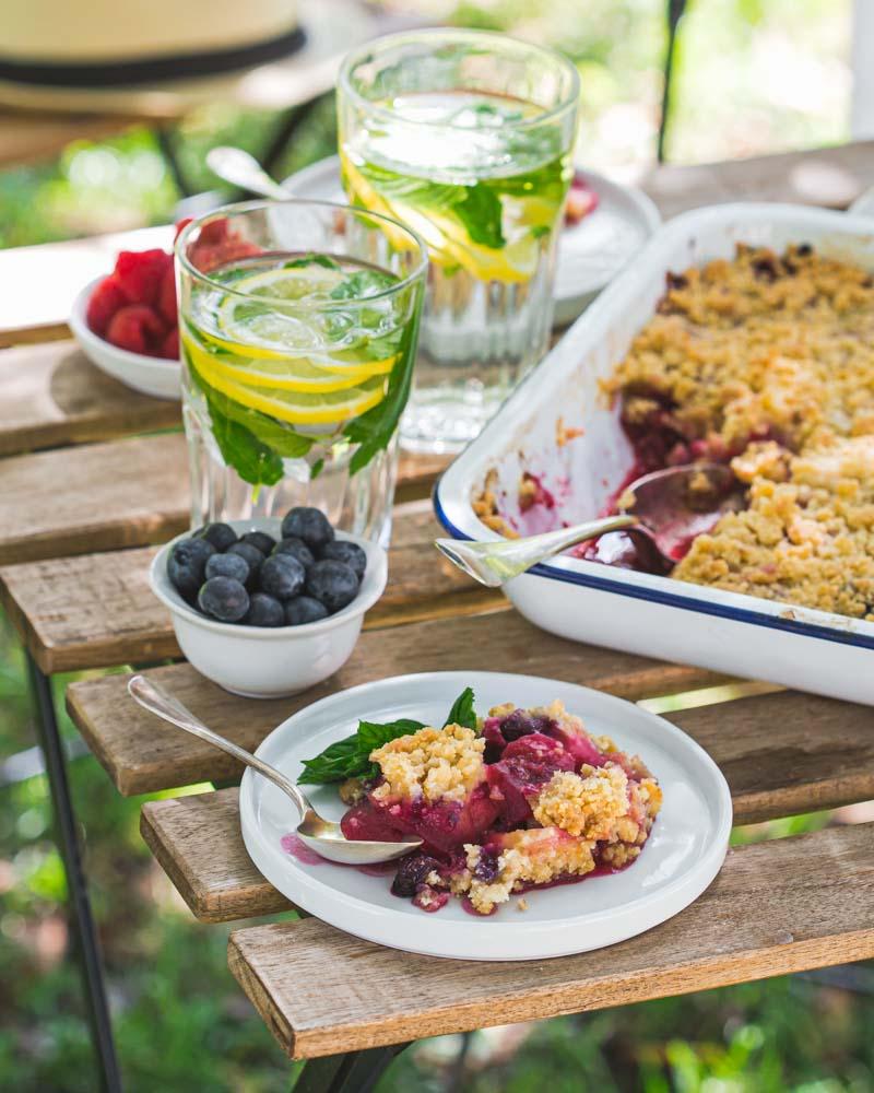 Assiette de crumble aux pommes et aux fruits rouges servie avec un eau infusée au citron et à la menthe fraîche. A savourer à l'heure du goûter.
