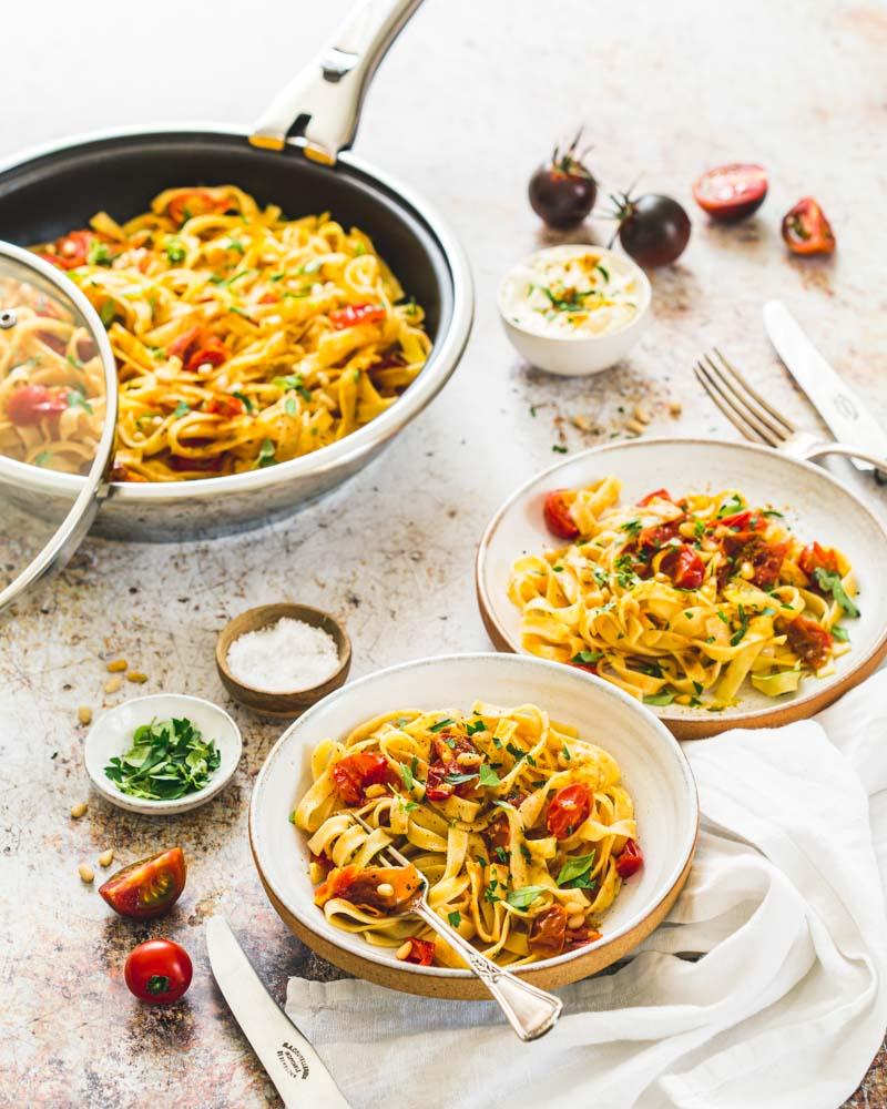 Assiettes de pâtes prêtes à être dégustées au tomates fraîches, curry, basilic, persil et pignons de pin.