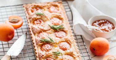 Tarte aux abricots et amandes servie avec du romarin