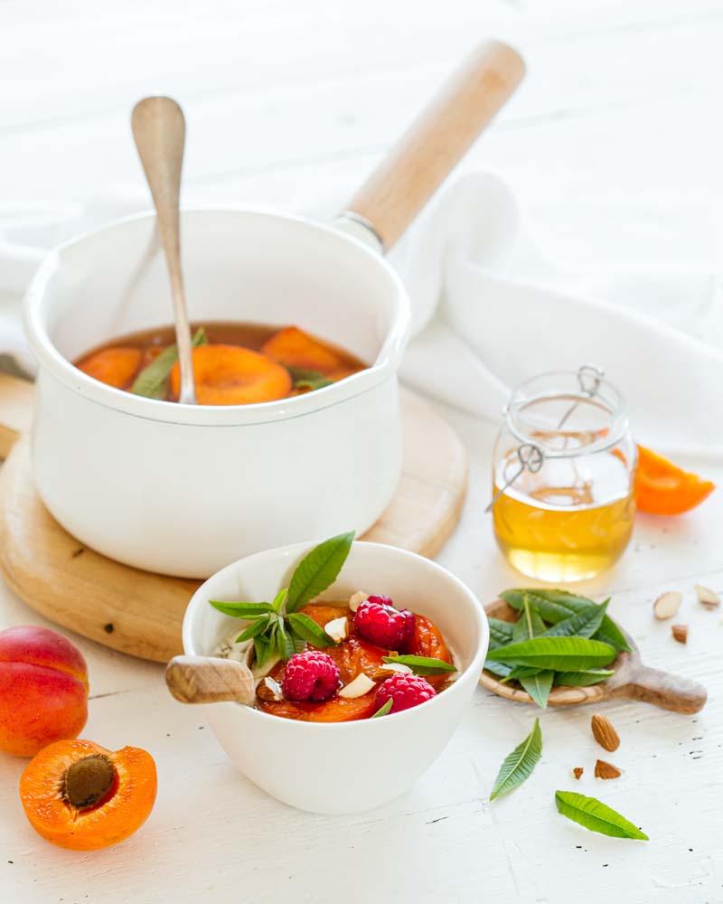 Casserole d'abricots pochés au miel servi avec des framboises et de la verveine citron.