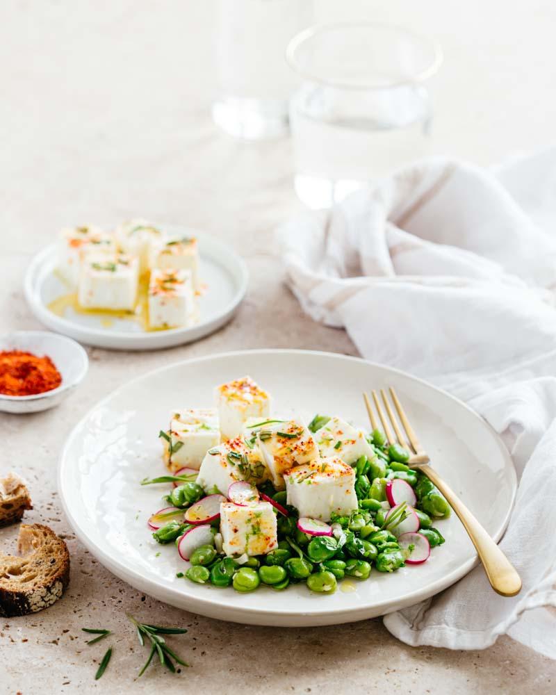 Salade de fèves, herbes fraîches et féta marinée : une entrée estivale relevée au piment d'Espelette et au zeste de citron vert.