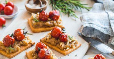 Tartelettes aux oignons confits et tomates cerise présentées sur une planche en bois