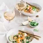 Assiettes de cabillaud et crevettes cuits au lait de coco façon thaï et servi avec du champagne