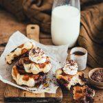 Gaufres vegan marbrées au chocolat et vanille posés sur une planche de bois et servis avec de la chantilly, copeaux de chocolat et sirop d'érable