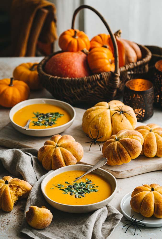 Assiette de soupe et petits pains au potiron en forme de petites citrouilles pour fêter Halloween à la maison