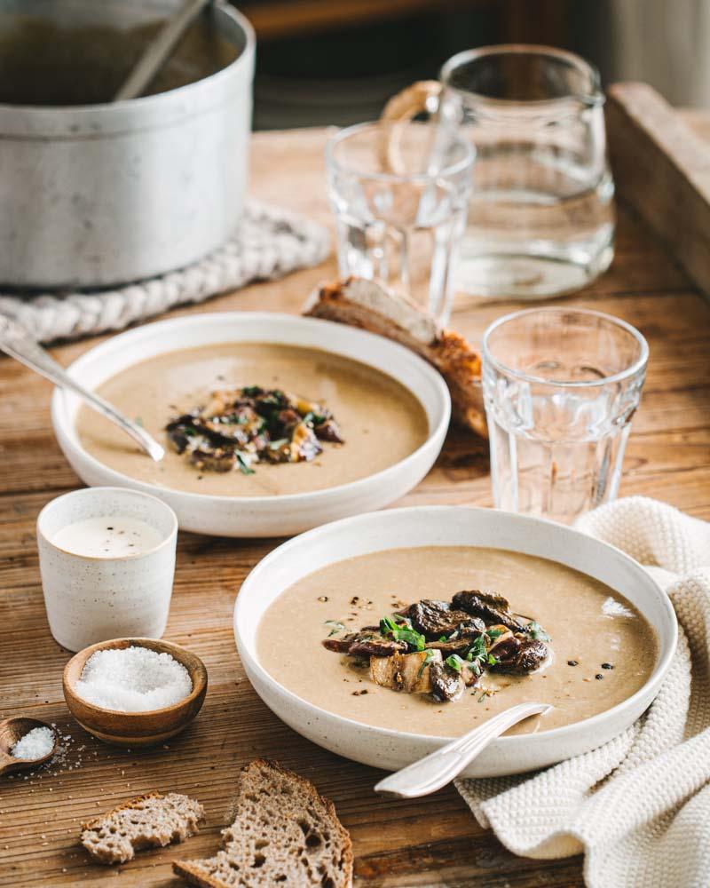 Assiettes creuses avec du velouté de cèpes aux châtaignes avec des cèpes poêlés en persillade et crème liquide. Une recette d'automne facile et réconfortante pour un dîner végétarien.