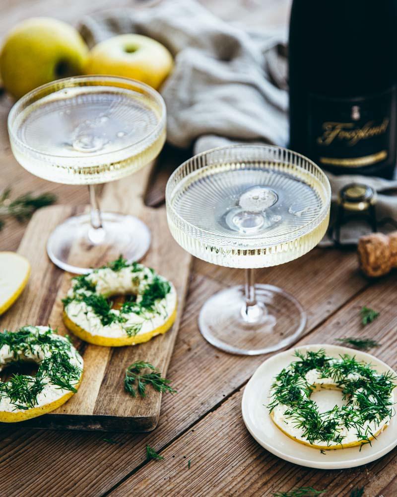 Idée apéritif sans cuisson : des lamelles de pommes recouvertes de fromage frais et d'aneth. A servir avec une coupe de champagne pour un apéritif chic.