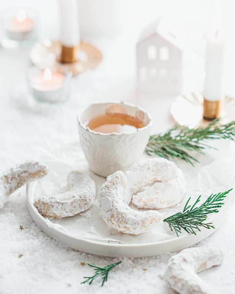 Assiette de biscuits de noël en forme de croissant de lune aux amandes et à la vanille que l'on appelle Vanille Kipferln. Servis avec une tasse de thé.
