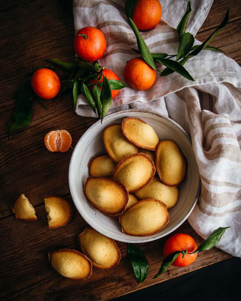 Assiette de madeleines au zeste d'orange vues de haut accompagnées de clémentines sur une table en bois.