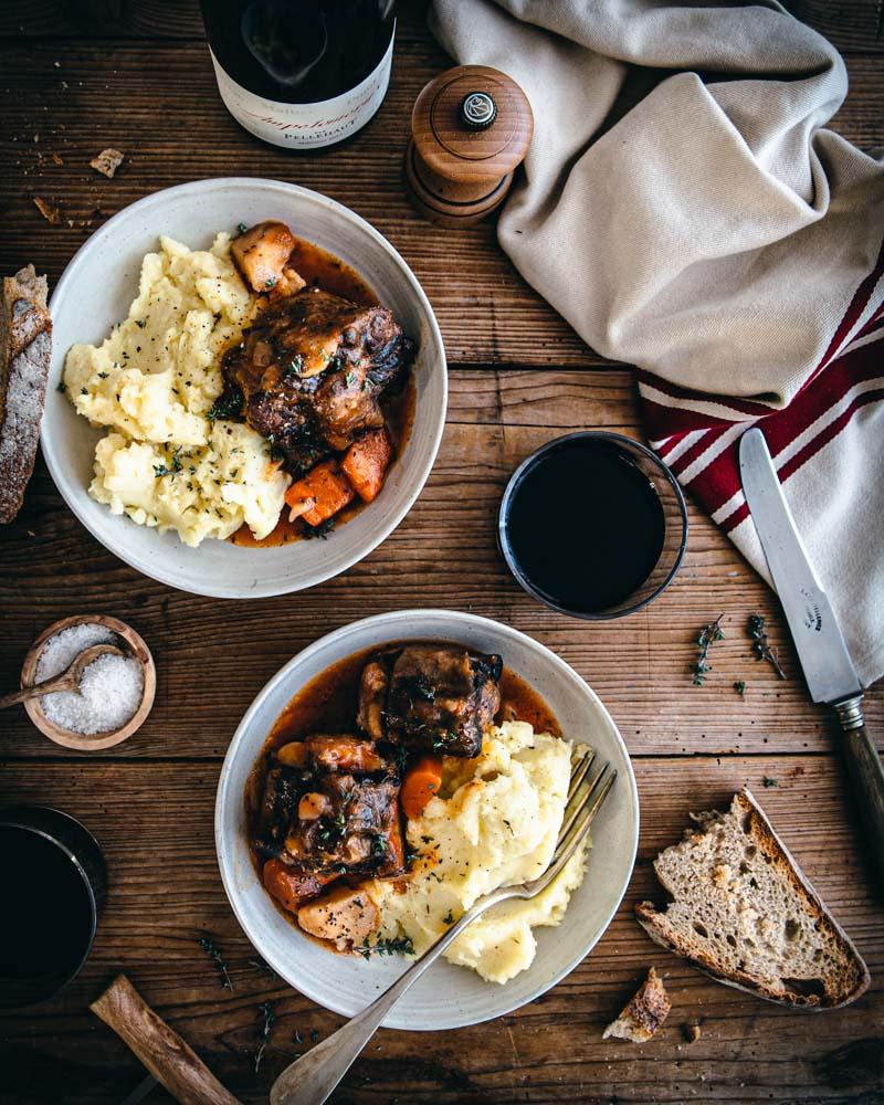 Vue de haut de deux assiettes garnies de queue de boeuf mijotées à la sauce tomate accompagnées de purée de pomme de terre. Avec ce plat est présenté du pain grillé, du sel et du vin rouge.