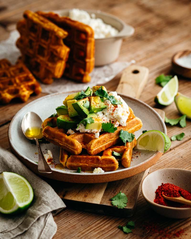 Assiette de gaufres de patate douce garnies avec des dés d'avocat au citron vert et la ricotta au piment d'Espelette. Un plat végétarien facile et rapide à faire.