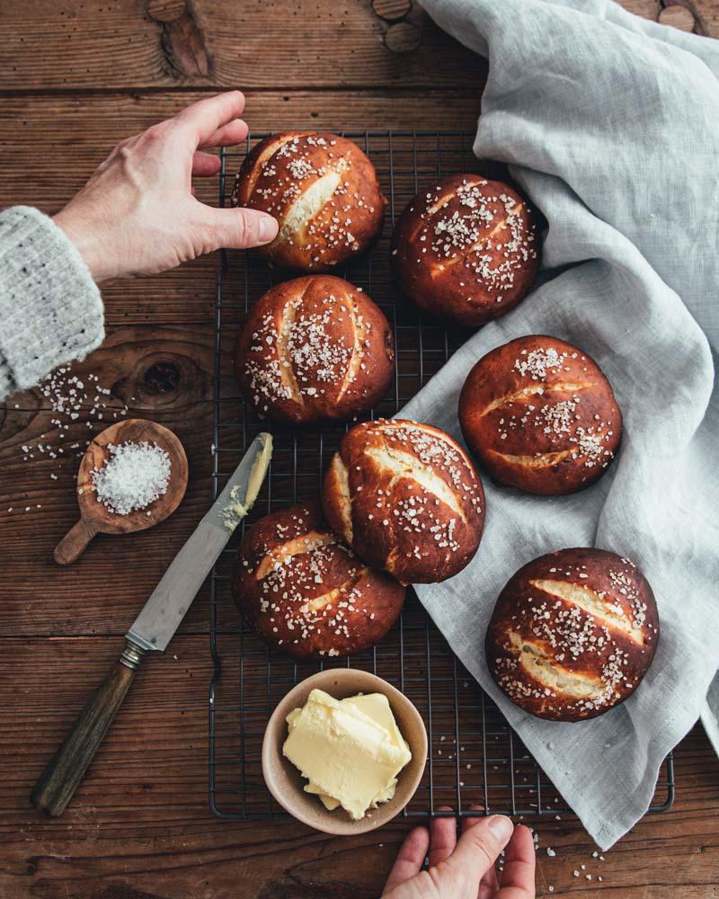 Photo de petits pains bretzels vue de haut avec une main essayant d'en attraper un. Servi avec une coupelle de beurre.