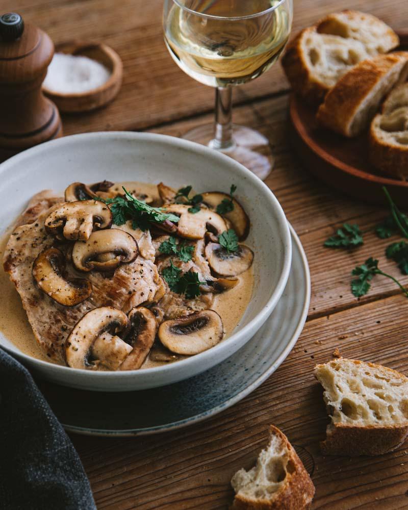 Assiette de noix de veau grillée garnie de lamelles de champignons de Paris dans une sauce à la crème