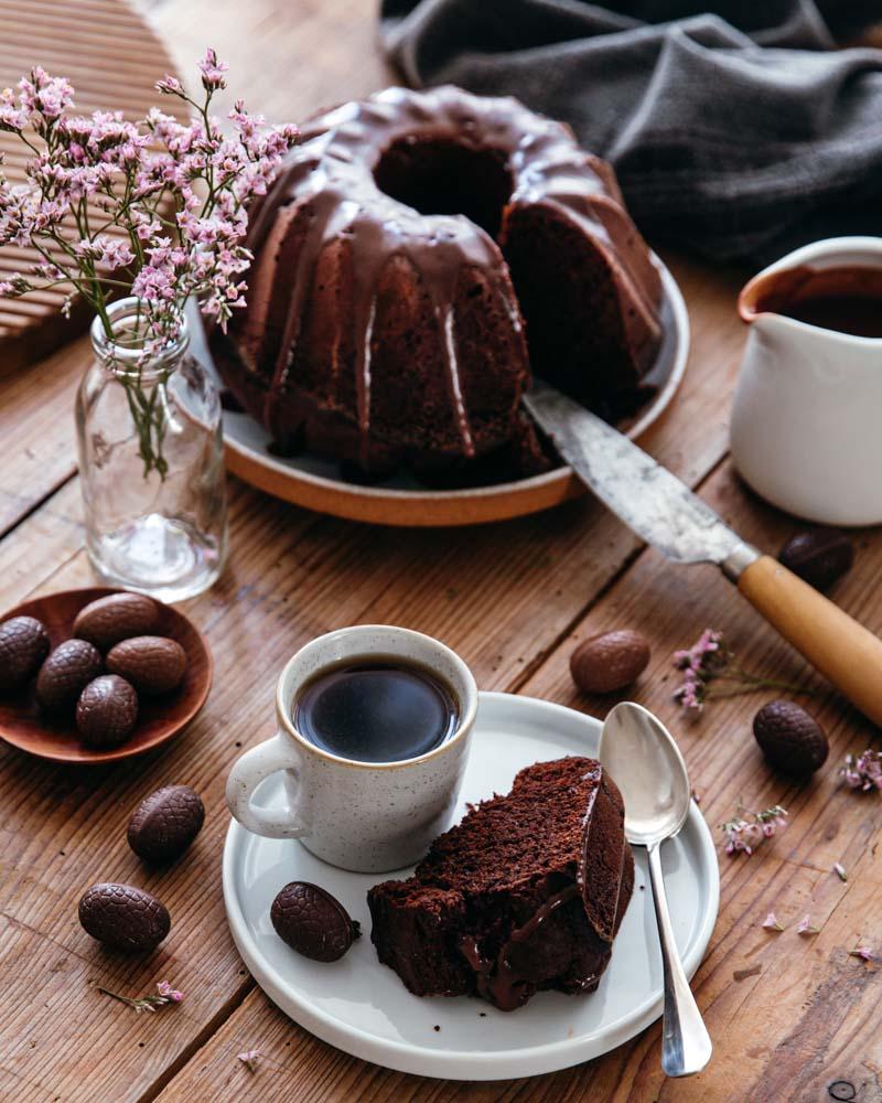 Part de gâteau au chocolat découpée et servie avec une tasse de café sur une table en bois, avec décor de pâques en chocolat