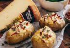 Pommes de terre farcies au fromage et aux lardons avec une part de Vacherin Fribourgeois en fond. A servir avec une salade verte