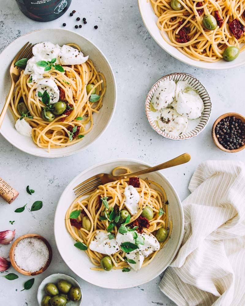 vues de haut garnies de spaghettis cuisinés avec des olives vertes, tomates séchées et de la mozzarella.