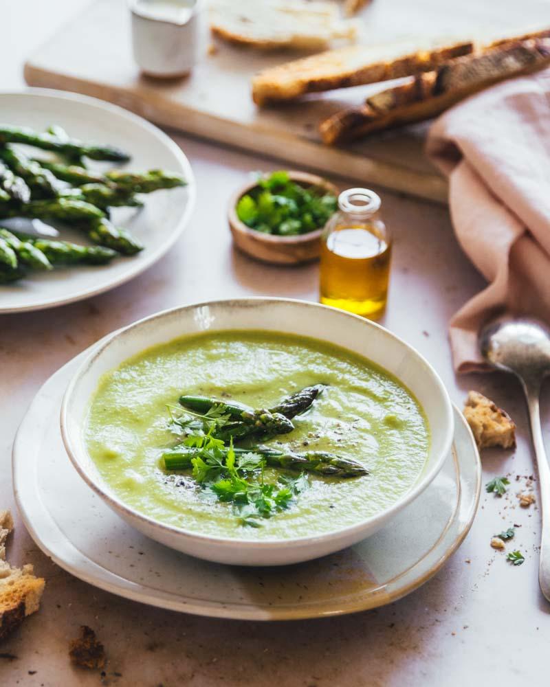 Bol de velouté d'asperges vertes et petits pois accompagné de pain grillé. Un délice pour le printemps, un repas sain et de saison.