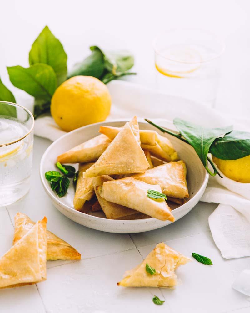 Assiette de briouates à la menthe et à la féta dans une ambiance estivale avec une boisson fraîche au citron