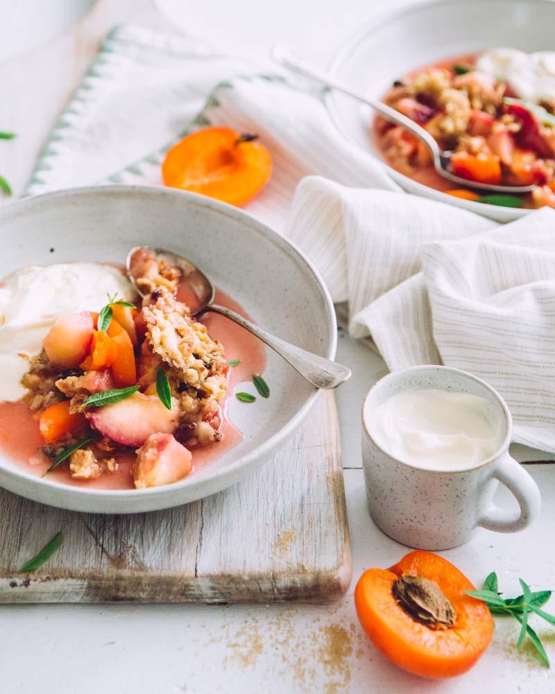 Assiette creuse garnie de crumble aux pêches, nectarines et abricots au muesli avec un peu de crème fraîche.