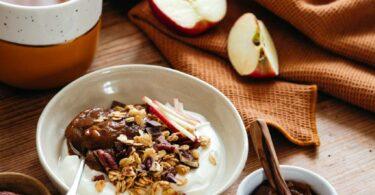 Petit déjeuner dans un bol avec céréales et compote de pruneaux aux pommes