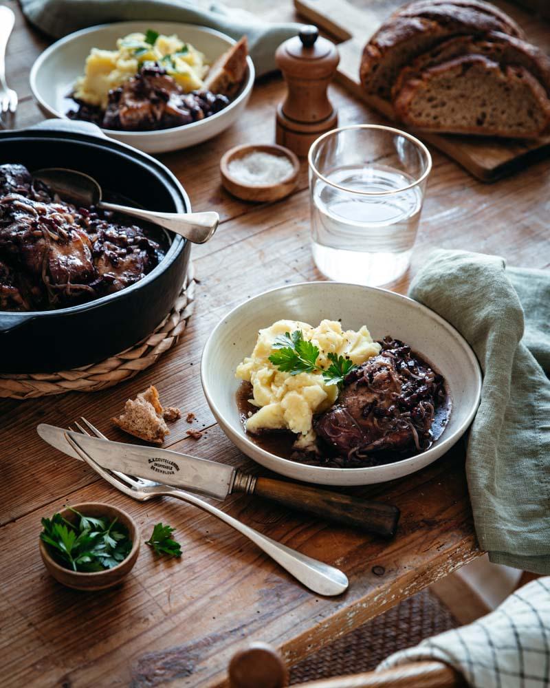 Assiette de lapin à la bourguignonne ,posée sur une table en bois, servie avec une purée de pommes de terre. Ambiance rustique.